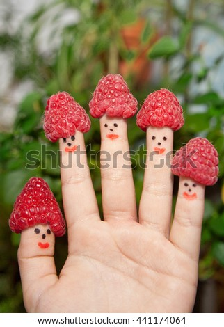 Child's hand with raspberries on fingers