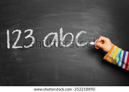 "Child's hand writing ""123 abc!"" on blackboard - stock photo"