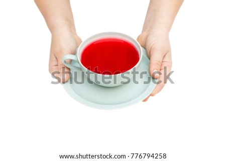 Child's hands holds cup of tea on saucer. Isolated on white.