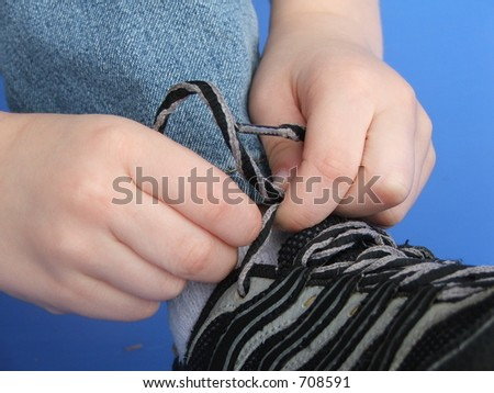 Child's hands learning to tie shoes