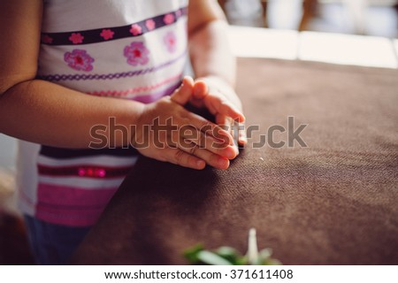 child's hands on table with brown tablecloth - stock photo