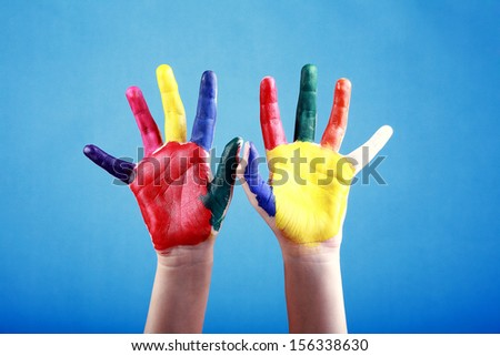 Child's hands painted with multicolored finger paints on blue background   - stock photo