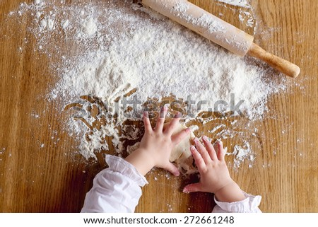 Child's hands playing with the flour - stock photo