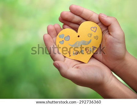 Child's hands with a Father's Day card - stock photo