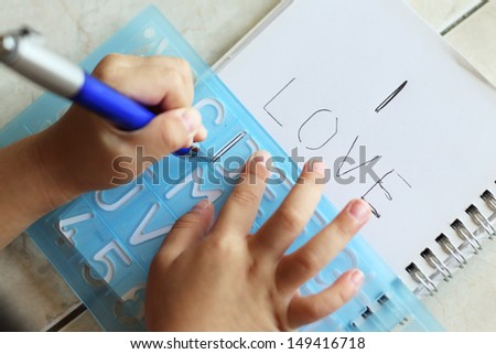 Child's hands writing a message on a paper using a stencil - stock photo