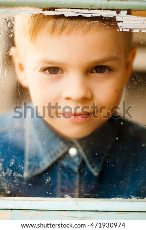 Child's happy face . Portrait of a Cute Kid.  little boy with short blond hair and brown yeas. Beautiful little boy seven years posing with a hat and denim shirt. Smailing boy