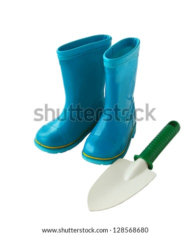 Child's little blue rubber gumboots with a shovel on a white background - stock photo