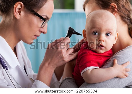 Child's otolaryngologist doing ear examination of infant - stock photo