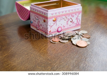 Child's savings coins in front of a money box in pounds sterling - stock photo