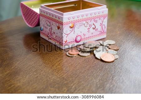 Child's savings. Pile of money with open kid's money box. Budget saving concept. - stock photo