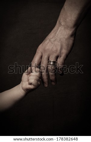 Child's small hand holding finger of his father, dark key - stock photo