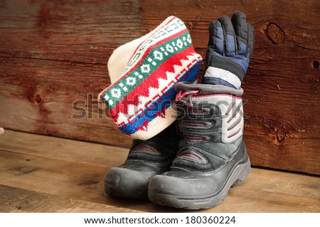 Child's snow boots with a colorful knitted winter cap and thick warm gloves standing ready in a rustic wooden cabin to venture out into the cold winter weather - stock photo