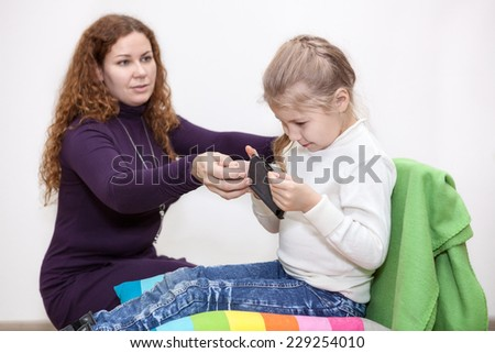 Child safety on the Internet, the girl saw forbidden content, mom takes away smartphone - stock photo