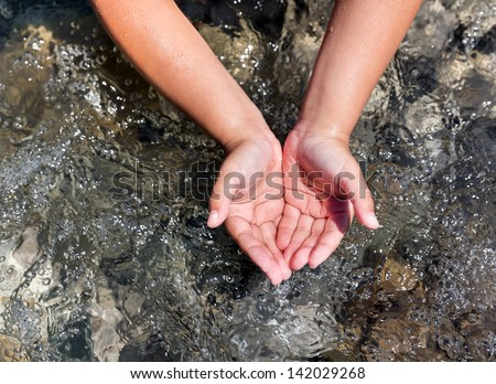 Child scoops up clear water with his hands in river - stock photo