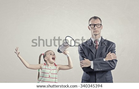 Child screaming with megaphone to adult indifferent man  - stock photo