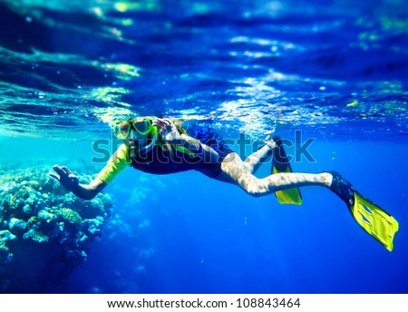 Child scuba diver with group coral fish in  blue water. - stock photo