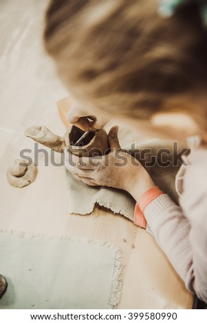 Child sculpts a small jar of wet clay