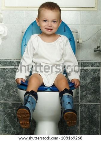 Child seated on toilet - stock photo
