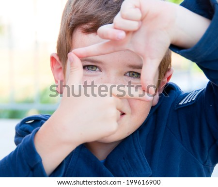 Child showing a square frame with his hands - stock photo