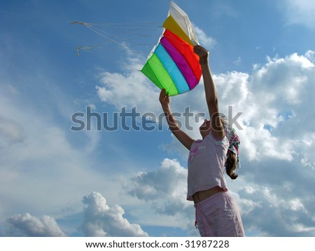 child silhouette starting kite against cloudy sky - stock photo