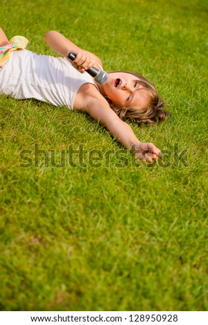 Child singing with microphone and lying on grass - outdoor lifestyle - stock photo