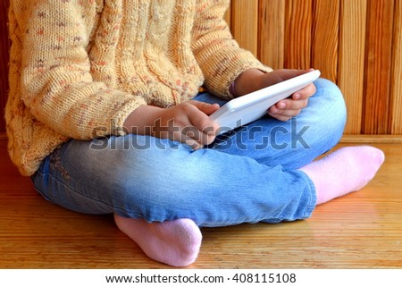 Child sits holding a tablet in hands. Wooden background
