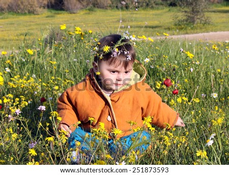 Child sits in a meadow among the flowers