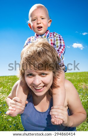 child sits on his mother's shoulders