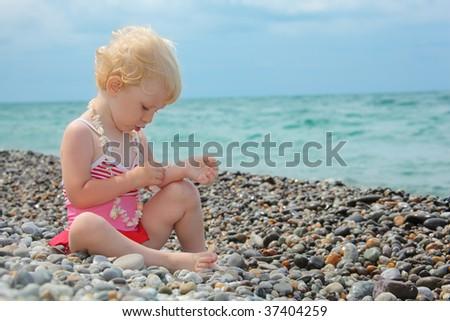 child sits on pebble beach - stock photo