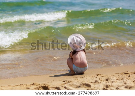 Child sits with his back to the camera on the shore of a tropical beach, watching the waves. Selective focus on the baby. Space for text.