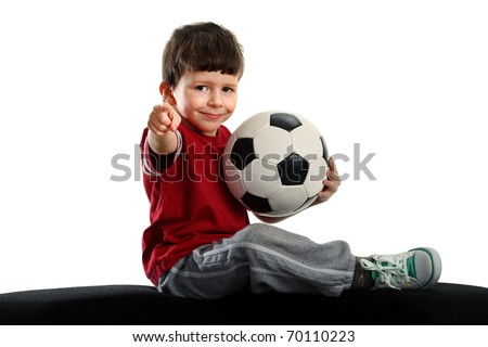 child sits with soccer ball and shows the finger at the camera, isolated on white background