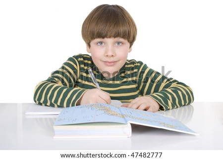 Child sitting at table and doing homework