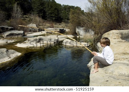 Child sitting at the shore of a river fishing with a bamboo rod