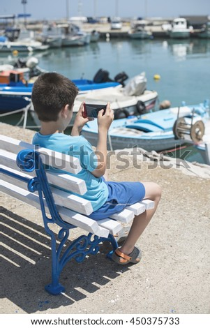 Child sitting on a bench on the beach in front of boats.