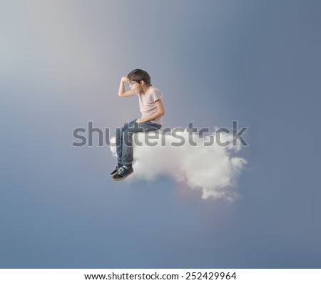 Child sitting on a cloud  - stock photo