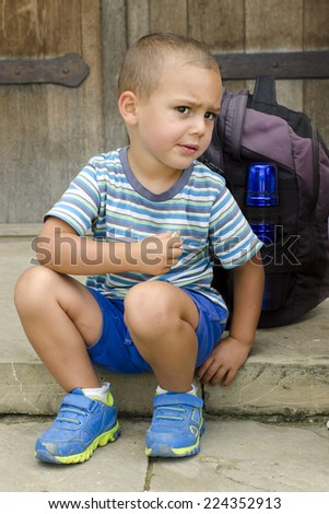 Child sitting on a step outside, snacking and resting during a walk trip or trek.