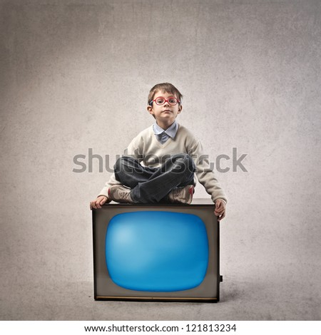 Child sitting on a television - stock photo
