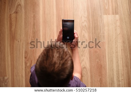 child sitting on a wooden base and holds a smart phone, a top view