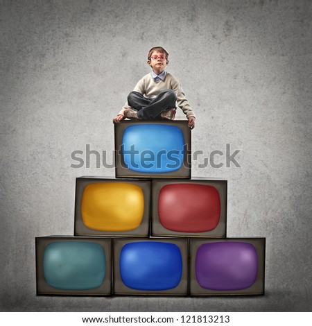 Child sitting on many televisions