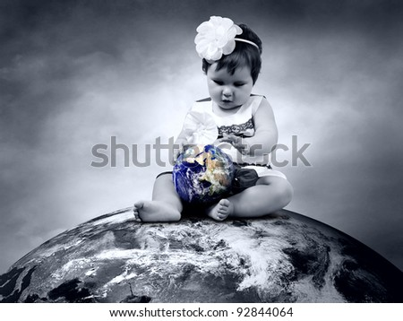 Child sitting on the Planet Earth with globes in hands - stock photo