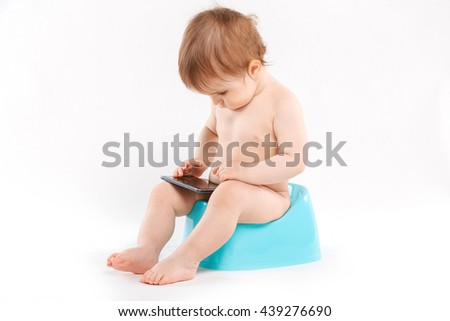 child sitting on the potty phone on a white background - stock photo