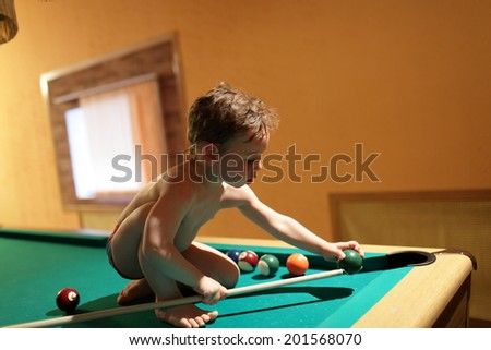 Child sitting with billiard cue on the pool table - stock photo