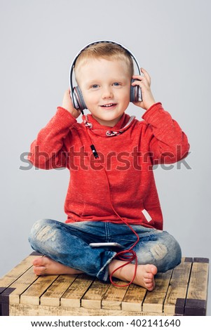 Child sitting with crossed legs and listening to music - stock photo