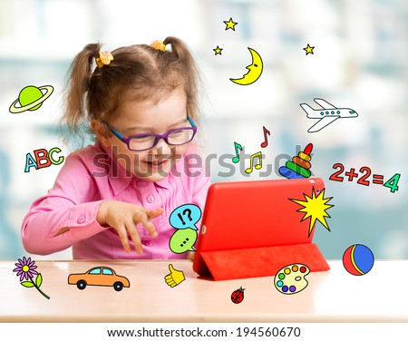 Child sitting with tablet computer and learning or playing with great interest - stock photo