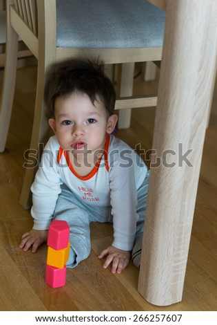 Child sitting with toy blocks on the floor by wooden chair