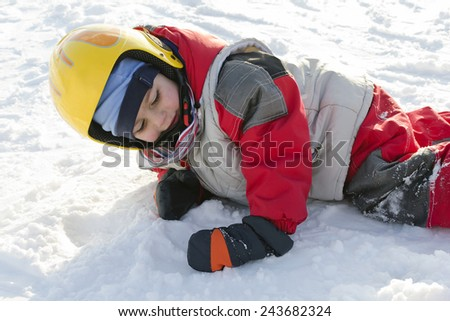Child skiing lying on a snow after falling when learning skiing, trying to get up - stock photo