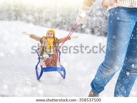 Child sledding. Parent rolls the child on a sled. Little girl enjoying a sleigh ride. Family plays outdoors in snow. Outdoor fun for family winter vacation. - stock photo