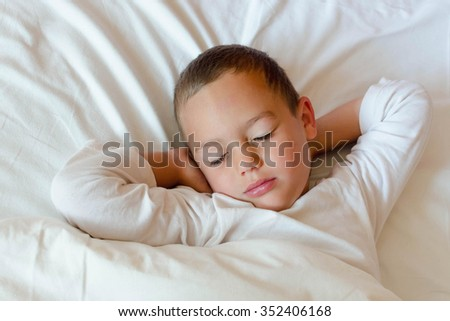 Child sleeping in bed in white sheets