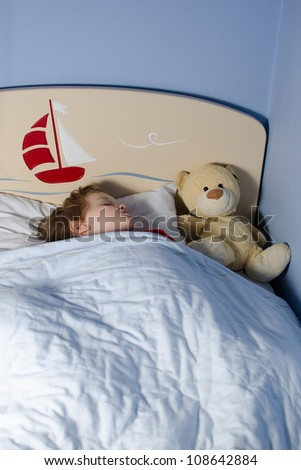 Child sleeping in his bed with teddy bear - stock photo
