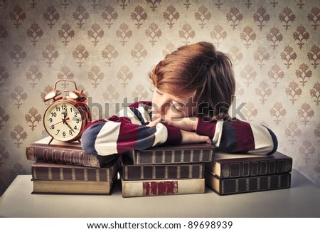 Child sleeping on a stack of books beside an alarm clock - stock photo